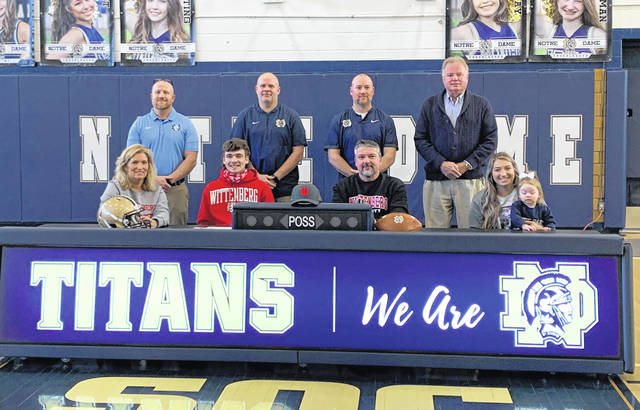 Notre Dame senior Caleb Nichols, seated left center, signed to continue his academic and football career at Wittenberg University located in Springfield at a signing ceremony last Friday.