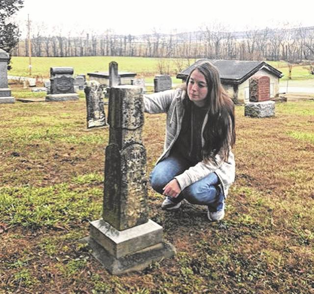 Girl Scout, Katie Rigsby, kneeling by one of the many stones that she worked on and recorded for Stockdale Cemetery.