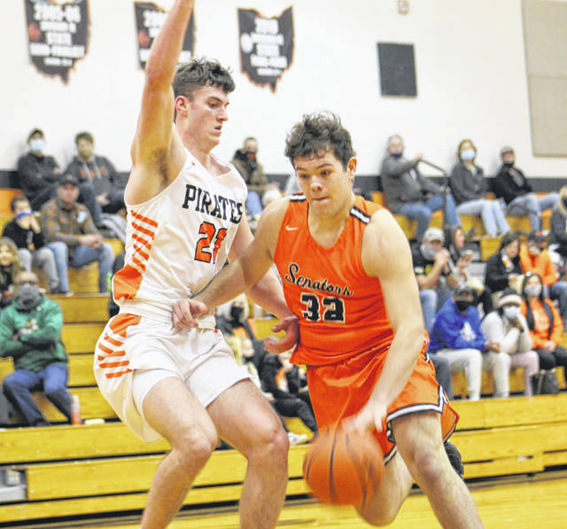 West's Jacob Davis (32) looks to drive past Wheelersburg's Carter McCorkle (21) during Friday night's Southern Ohio Conference Division II boys basketball game at Wheelersburg High School.
