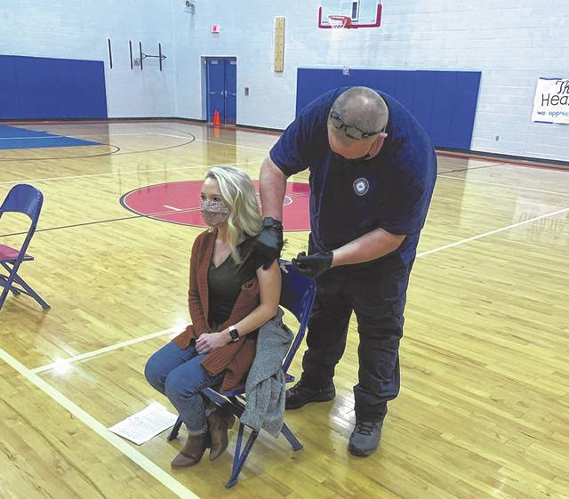 Portsmouth City Elementary Guidance Counselor, Ali Shultz receiving her vaccine from a member of the Portsmouth City Fire Department.