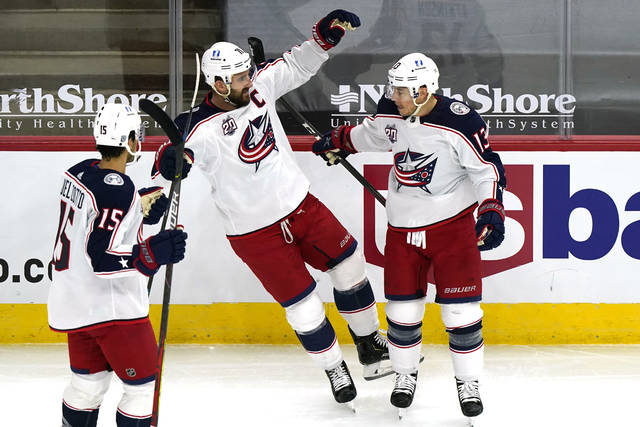 Columbus Blue Jackets right wing Cam Atkinson, right, celebrates with defenseman Michael Del Zotto, left, and left wing Nick Foligno after scoring a goal against the Chicago Blackhawks during the first period of an NHL hockey game in Chicago, Thursday, Feb. 11, 2021. (AP Photo/Nam Y. Huh)
