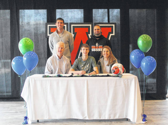Wheelersburg High School senior Aaron Jolly, seated center, announces his intention to play college soccer for Mount Vernon Nazarene University. Seated with Jolly are father Scott Jolly (left) and mother Maria Jolly (right); standing are Mount Vernon Nazarene University men's soccer coach Zach Ganzberg (left) and Wheelersburg High School boys soccer head coach Jon Estep (right).