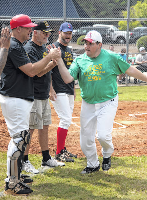 The young man in green is one of the Alternative Baseball players and those in black are former professional baseball players who played them.