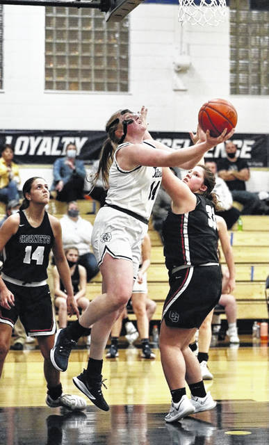 Notre Dame's Claire Detwiller (14) goes up for a reverse layup over Coal Grove's Jaidyn Griffith (33) and Kaleigh Murphy (14) during Tuesday night's non-league girls basketball game at Notre Dame High School.
