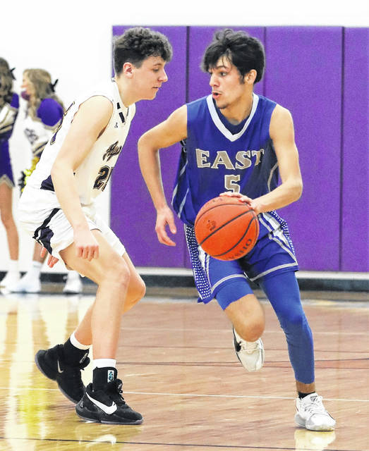 East's Austin Baughman (5) looks to drive around Ironton St. Joseph's J.C. Damron during Saturday's Southern Ohio Conference Division I boys basketball makeup game.