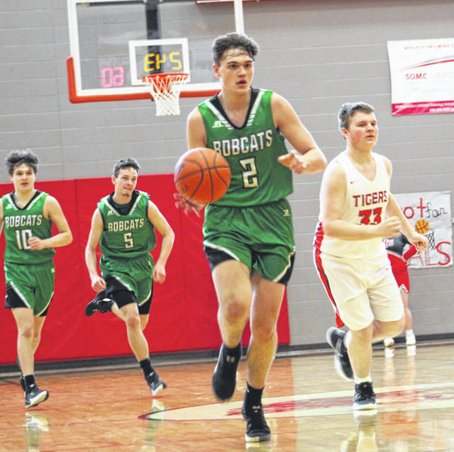 Green's Levi Sampson leads a fast break as Bobcat teammates Levi Blevins (10) and Ethan Huffman (5) trail the play during the Bobcats' Southern Ohio Conference Division I boys basketball game against New Boston on Saturday at New Boston High School's Homer Pellegrinon Gymnasium.