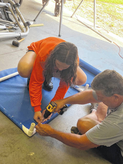 Savannah Williams and her father, Mark making the beds.