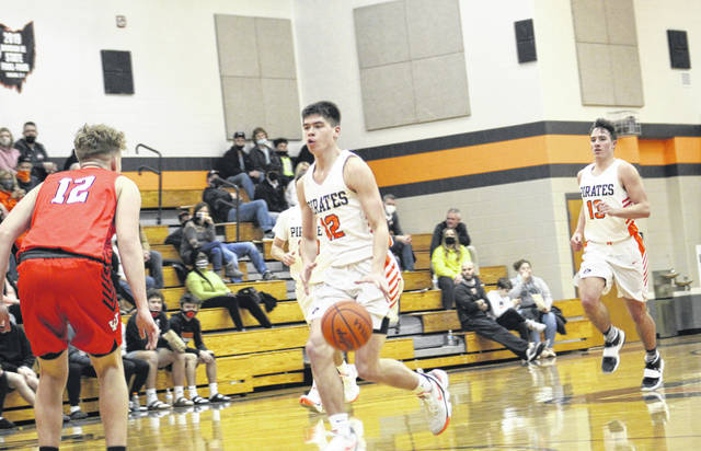 Wheelersburg's Matthew Miller (12) leads a fast break as Eli Swords (13) trails the play and Jackson's Tristan Prater defends during Saturday night's non-league boys basketball game at Wheelersburg High School.