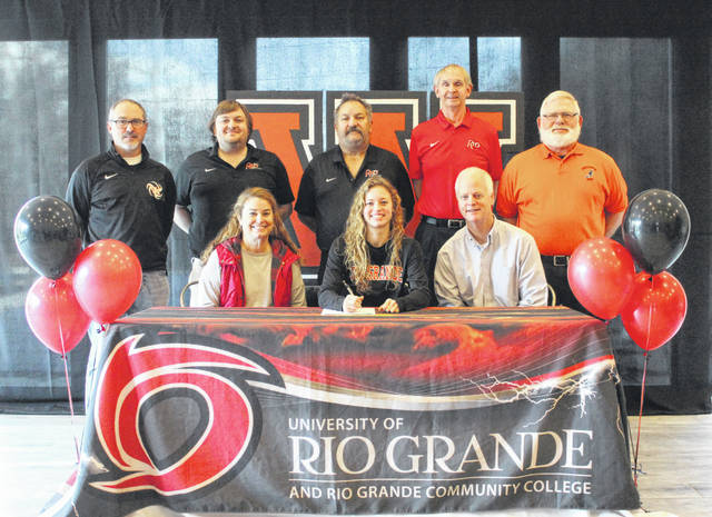 Wheelersburg High School senior Lauren Jolly, seated center, announces her intention to play college volleyball and run track and field for the University of Rio Grande. Seated with Jolly are mother Maria Jolly (left) and father Scott Jolly (right); standing are, from left, Wheelersburg High School volleyball coach Allen Perry, University of Rio Grande track and field assistant coach Jordan Cunningham; University of Rio Grande track and field assistant coach Glen Queen, University of Rio Grande track and field head coach Bob Willey and Wheelersburg High School track and field coach Paul Boll.