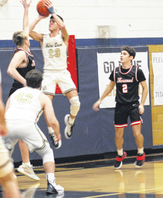 Notre Dame's Dylan Seison (23) shoots a jumper over New Boston's Kyle Sexton as Tiger teammate Grady Jackson (2) looks on during Friday night's Southern Ohio Conference Division I boys basketball game at Notre Dame High School.