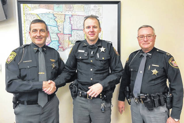 (Left to right): Scioto County Sheriff David Thoroughman, Deputy Martin Potts, and Captain Robert Woodford as Thoroughman is thanking Potts for a 'job well done.'