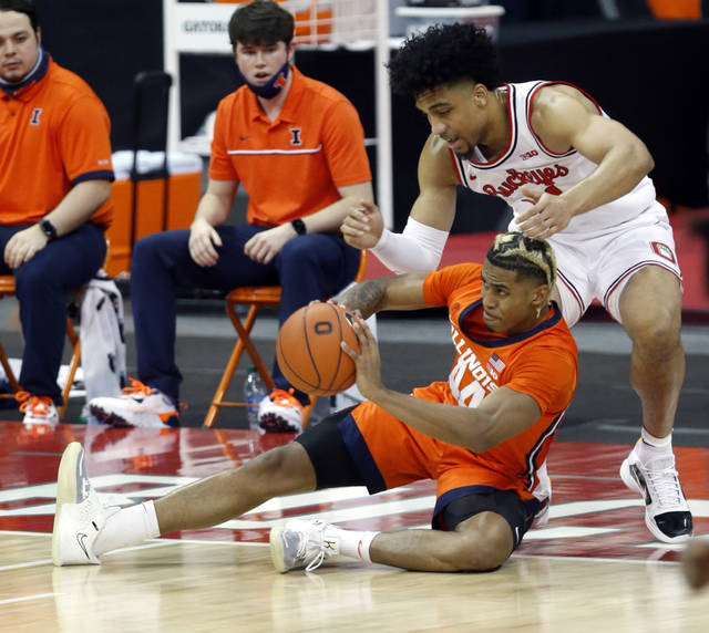 Illinois guard Adam Miller, bottom, passes against Ohio State forward Justice Sueing during the first half of an NCAA college basketball game in Columbus, Ohio, Saturday, March 6, 2021. (AP Photo/Paul Vernon)