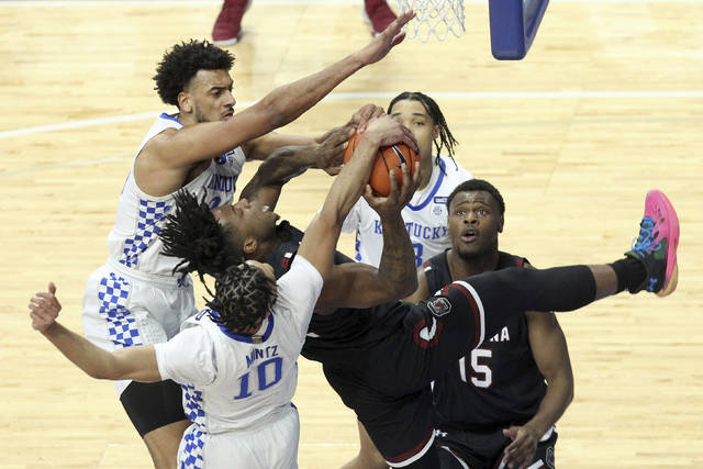 South Carolina's Trae Hannibal, center, has his shot blocked by Kentucky's Davion Mintz (10) and Olivier Sarr, top left, during the first half of an NCAA college basketball game in Lexington, Ky., Saturday, March 6, 2021. (AP Photo/James Crisp)