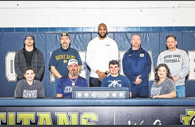 Notre Dame High School senior Austin Vaughters, seated second from right, announces his intention to swim collegiately for Shawnee State University. Seated with Vaughters are, from left, sister Savanna Vaughters, father Jody Vaughters and mother Cashawna Vaughters; standing are, from left, former Notre Dame Junior High School swim coach Jacob Taylor, Notre Dame High School swim coach John Taylor, Shawnee State University head swim coach Gerald Cadogan, Notre Dame High School Athletic Director Bob Boldman and C.J. Piatt.