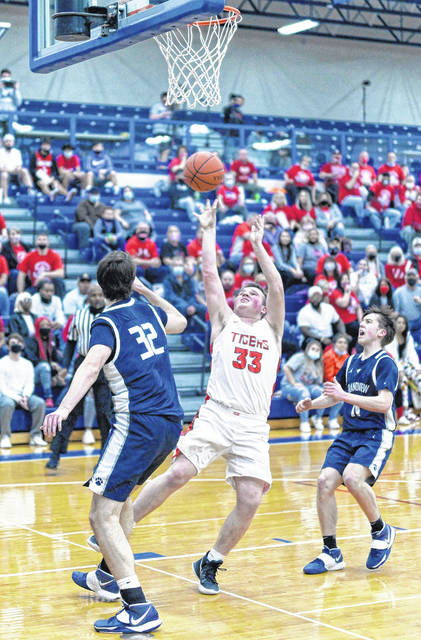 New Boston's Brady Voiers (33) puts up a shot over Grandview Heights' Grant Culbertson (32) during last week's Division IV boys basketball regional semifinal game at Southeastern High School.