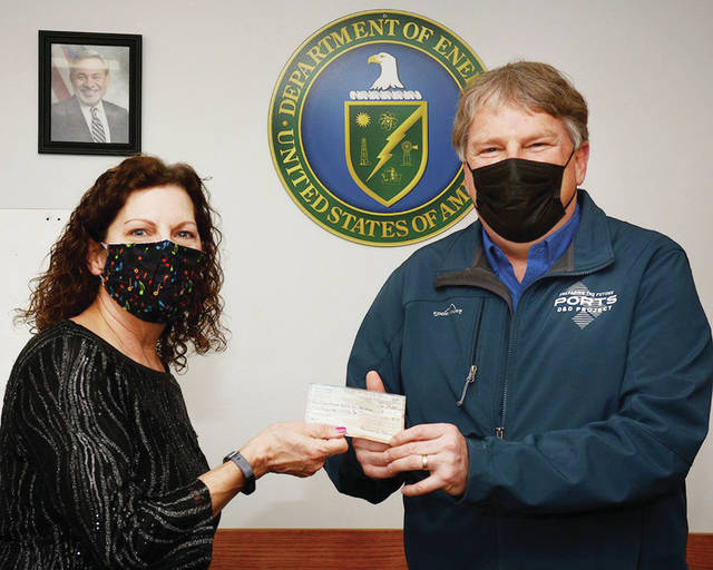 Mimi Clausing presents a $550 check to Fluor-BWXT Site Director JD Dowell for the Christmas Gifts for Children Program which has been ongoing at the plant for nearly 30 years. Clausing provided the donation upon her retirement after 38 years of service at the PORTS site.