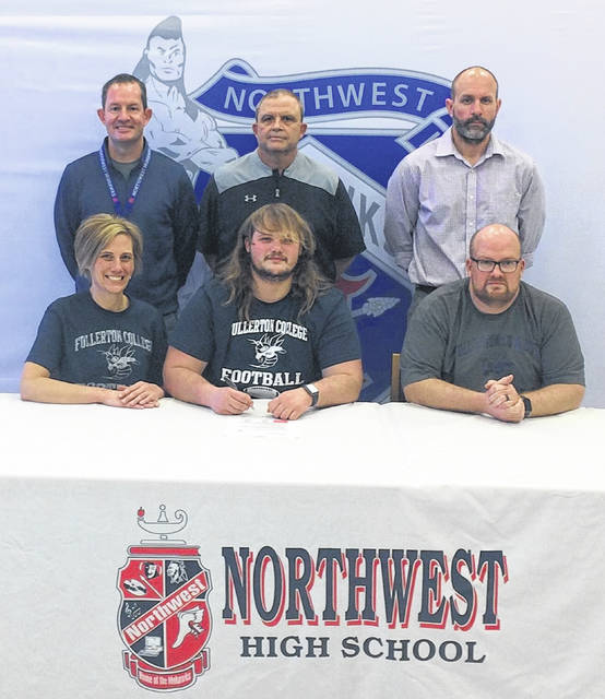 Northwest High School senior Caleb Crabtree, seated center, announces his intention to play college football for Fullerton College (Calif.). Seated with Crabtree are mother Tara Crabtree (left) and father and Northwest High School head football coach Bill Crabtree (right). Standing are, from left, Northwest High School assistant football coach Bill Shannon; Northwest High School Athletic Director Dave Frantz and Northwest High School assistant football coach Brooks Fry.
