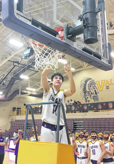 Valley's Colt Buckle (12) cuts down the net following the Indians' 62-40 Division IV sectional championship victory over visiting Waterford on Saturday night.