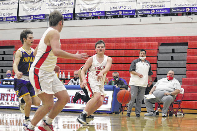 New Boston junior Brady Voiers (33) assists on a bucket by senior brother Tanner Voiers (3) during the Tigers' 71-51 win over Valley in Saturday night's Division IV district championship.