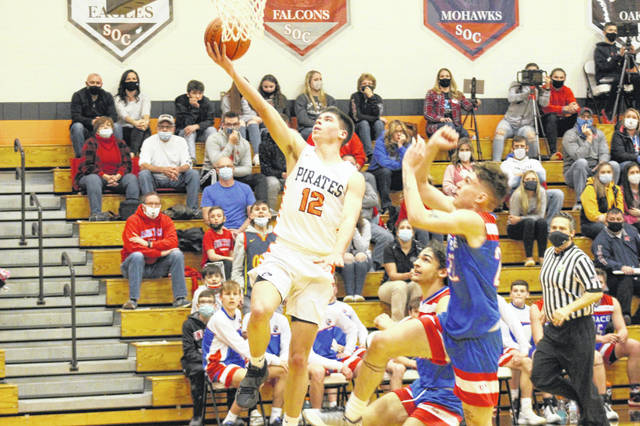 Wheelersburg senior Matthew Miller (12) finishes a transition layup during the Pirates' 70-32 win over Zane Trace in a Division III sectional championship.
