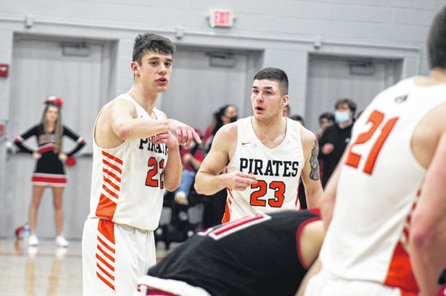 Wheelersburg seniors J.J. Truitt (22) and Gage Adkins (23) discuss strategy during a free-throw attempt in the late stages of their 66-59 win over Eastern Brown in a boys Division III district title game.