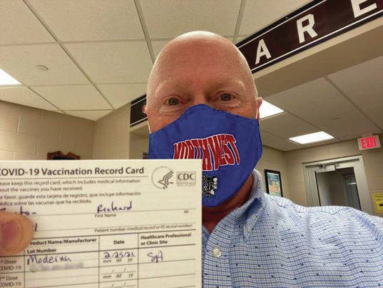 Principal Jason Burton showing his vaccination card.