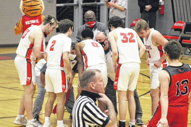 The New Boston coaching staff huddles with their players on the court during the pregame prior to Wednesday night's Division IV district semifinal versus South Webster.