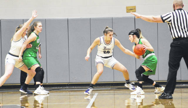 Notre Dame seniors Claire Dettwiller (14) and Isabel Cassidy (20) defend the post against Waterford during their Division IV district championship game on Saturday at Vinton County High School.