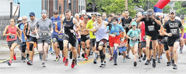 Runners begin the 2019 Kiwanis Run By The River in downtown Russell, Ky. The current COVID-19 pandemic has led to the 2021 race resulting in a virtual 5K, meeting guidelines on crowd size and social distancing.
