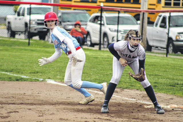 Portsmouth junior Madison Perry (14) looks to run the bases near Notre Dame first baseman Kyndall Ford (1) during the two's non-league meeting on Thursday in Portsmouth.