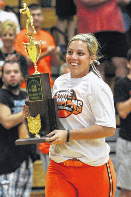 Laiken Salyers proudly carries the 2016 Division III state softball championship trophy into the Wheelersburg High School gymnasium.