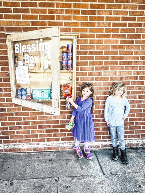 A couple of preschoolers from Clay filling the Blessing Box