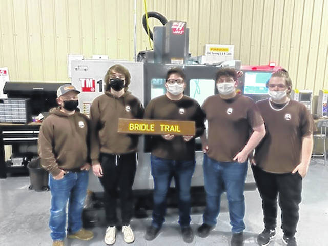 Left to Right: Brock Zimmerman, Jett Pahl, Gannon Knight, Owen Fitch, Aiden Cramer. (Not Pictured: Shane Dixon) In front of the CNC Machine used to make signs.