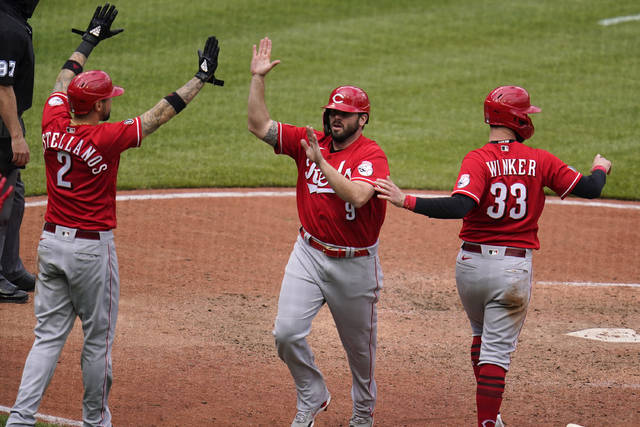 Cincinnati Reds' Mike Moustakas (9) is greeted by Nick Castellanos (2) and Jesse Winker after they all scored on a double by Eugenio Suarez off Pittsburgh Pirates relief pitcher Duane Underwood Jr. during the tenth inning of a baseball game in Pittsburgh, Wednesday, May 12, 2021.(AP Photo/Gene J. Puskar)