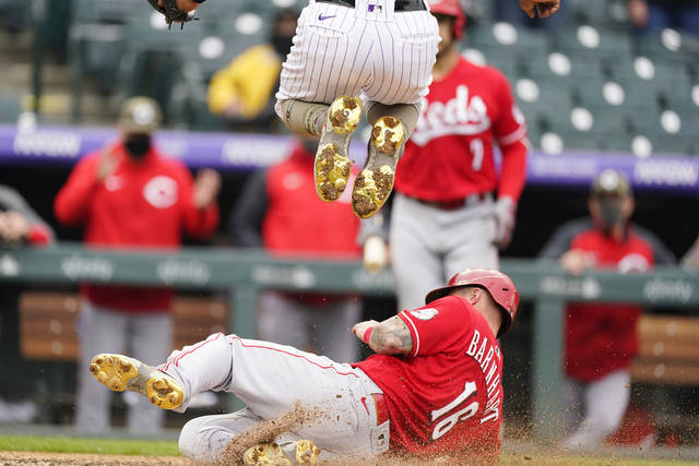 Cincinnati Reds' Tucker Barnhart, bottom, slides across home plate to score the tying run on a wild pitch by Colorado Rockies relief pitcher Mychal Givens, top, in the ninth inning of a baseball game Sunday, May 16, 2021, in Denver. (AP Photo/David Zalubowski)