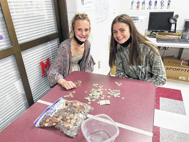 8th graders Ava Cronin and Maggie Risner counting coins that the 8th-grade history classes collected for the Adult Day Center in Portsmouth.