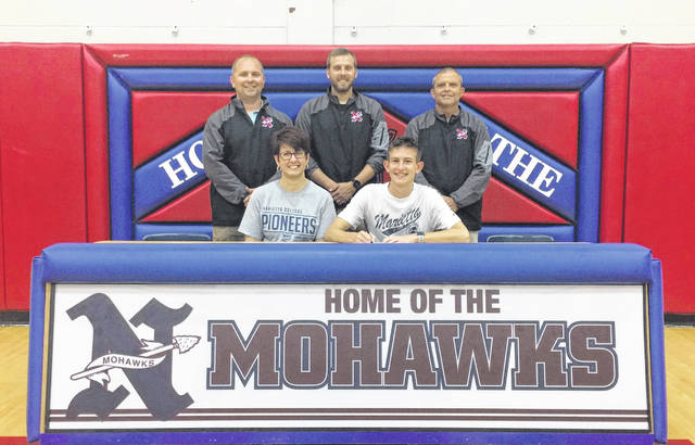 Gabe Morrell, seated right, announces his intention to run cross country and track and field for Marietta College. Seated with Morrell is mother Melissa Adams (left). Standing are, from left, Northwest High School assistant track and field coach Chris Enz, Northwest High School head cross country coach and assistant track and field coach Adam Schroeder and Northwest High School head track and field coach and athletic director Dave Frantz.