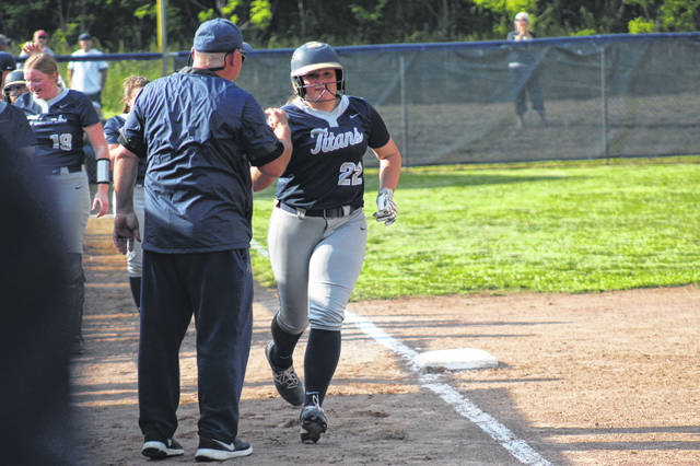 Notre Dame freshman Kaylor Pickelsimer (22) fist-bumps third base coach Tim Harr on her way to home plate after her three-run home run in the Lady Titans' 10-0 win over Belpre in a Division IV district semifinal.