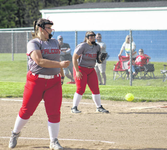 Minford's Addison Lute delivers a pitch to a Southeastern batter as twin sister and first baseman Harley Lute looks on.