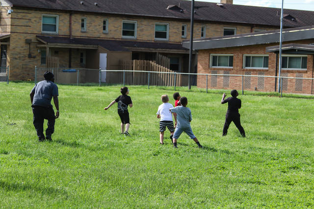 Children play in the field as their parents work on finding solutions to keeping it for the children.