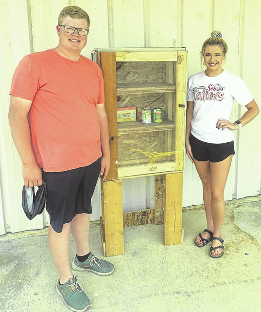"""Matthew Koverman with McKenna Higbee standing by the """"Blessing Box"""" he and his family built for the Minford community."""