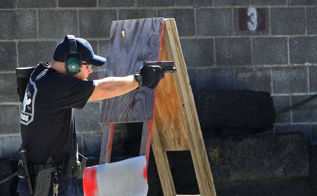 FILE—In this file photo from Oct. 8, 2013, police officer JR Lavish shoots a pistol during a police training exercise at the Eagle Creek Firearms Training Facility in Findlay, Ohio. After a 2016 shooting at Madison Local Schools in southwestern Ohio, a group of parents sued the district in September 2018 to prevent teachers from being armed without extensive training. The Ohio Supreme Court ruled Wednesday, June 23, 2021 that armed school employees must undergo an approved basic peace-officer-training program or have 20 years experience as a police officer. (Kelly Wilkinson/The Indianapolis Star via AP)