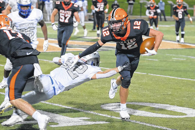 Wheelersburg senior Matthew Miller (12) stiff-arms a Ready defender during the Pirates' 31-21 win over the Silver Knights at Ed Miller Stadium during the 2020 OHSAA football playoffs.