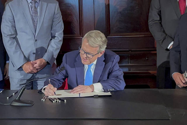 FILE - Ohio Governor Mike DeWine signs an executive order allowing college athletes in Ohio to earn money off their name, image and likeness at the Ohio Statehouse in Columbus, Ohio, in this Monday, June 28, 2021, file photo. The NCAA Board of Directors is expected to greenlight one of the biggest changes in the history of college athletics when it clears the way for athletes to start earning money based on their fame and celebrity without fear of endangering their eligibility or putting their school in jeopardy of violating amateurism rules that have stood for decades. (AP Photo/Farnoush Amiri, File)