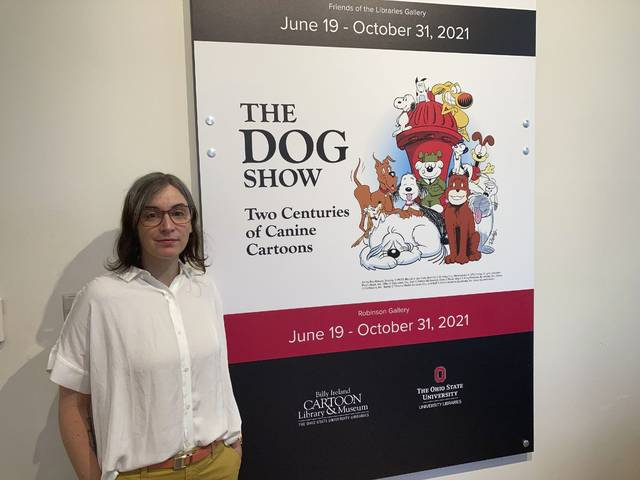 """Anne Drozd, museum coordinator at Ohio State University's Billy Ireland Cartoon Library Museum, stands at the entrance to the library's new exhibit, """"The Dog Show,"""" on Thursday, June 24, 2021, in Columbus, Ohio. Drozd said the genesis for the exhibit came when the late Brad Anderson, the creator of Marmaduke, donated his collection in 2018, including 16,000 original Marmaduke cartoons from 1954 to 2010. (AP Photo/Andrew Welsh-Huggins)"""