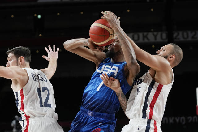 United States' forward Kevin Durant (7) and France's Evan Fournier, right, fight for control of the ball during a men's basketball preliminary round game at the 2020 Summer Olympics, Sunday, July 25, 2021, in Saitama, Japan. (AP Photo/Eric Gay)