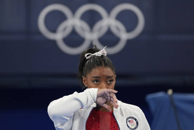 Simone Biles, of the United States, watches gymnasts perform after an apparent injury, at the 2020 Summer Olympics, Tuesday, July 27, 2021, in Tokyo. Biles withdrew from the team finals. (AP Photo/Ashley Landis)