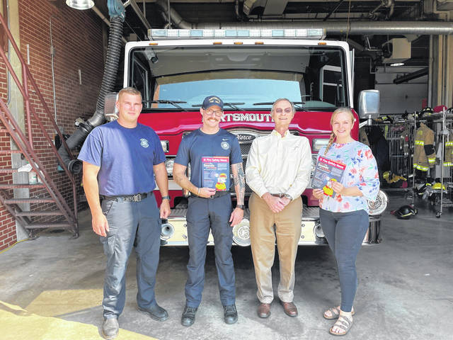 Far Left- Fire Fighter Joey Reinhardt, Lieutenant Kyle Moore, State Farm agent Jeff Smith, and Jeff's team member Sara Born. Local State Farm agent Jeff Smith donating a fire prevention kit to help firefighters educate the community about the sounds of fire safety.