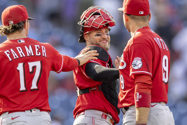 Cincinnati Reds shortstop Kyle Farmer (17), catcher Tucker Barnhart, center, and first baseman Joey Votto (19) celebrate after they defeated the Philadelphia Phillies in a baseball game, Sunday, Aug. 15, 2021, in Philadelphia. (AP Photo/Laurence Kesterson)