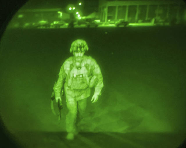 In this image made through a night vision scope and provided by the U.S. Army, Maj. Gen. Chris Donahue, commander of the U.S. Army 82nd Airborne Division, XVIII Airborne Corps, boards a C-17 cargo plane at Hamid Karzai International Airport in Kabul, Afghanistan, Monday, Aug. 30, 2021, as the final American service member to depart Afghanistan. (Master Sgt. Alexander Burnett/U.S. Army via AP)